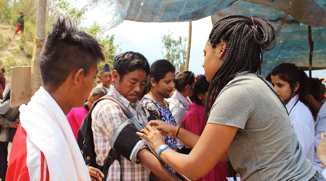 Medicine volunteer measures the blood pressure of a local in Nepal